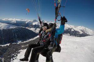 Gleitschirmflug über verschneite Skipisten in Davos