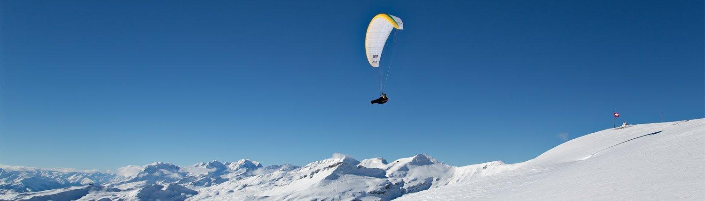 Winterlicher Gleitschirmflug vor der Schweizerfahne