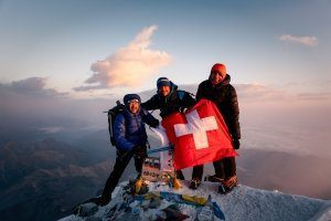 Elbrus HikeFly summit photo with Swiss flag